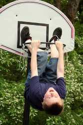 Junge ist in einen Basketballkorb geklettert