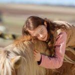 Ein Mädchen schmiegt sich an ihr Pferd