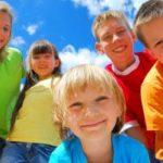 Eine Gruppe fröhlicher Kinder in bunter Sommerkleidung.