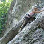 Ein Kind beim Klettern an einer Felswand
