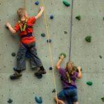 Junge und Mädchen beim Klettern an einer Kletterwand