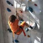 Kind an einer Kletterwand