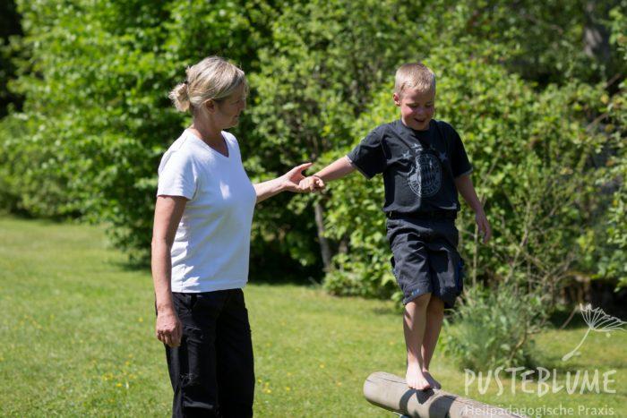 Ein Junge balanciert an der Hand von Birgit Darda.
