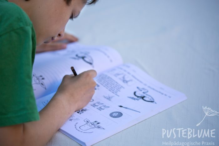 Ein Junge arbeitet im Heft vom Therapieprogramm Gustav Giraffe.