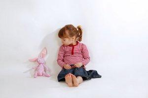 Kleines Mädchen mit Kuscheltier Hasen
