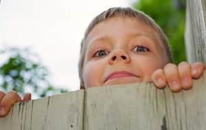 Neugieriges Kind spitzt über Bretterzaun