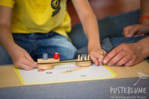 Ein Junge arbeitet mit dem Mechaniko-Kasten während der Übungsbehandlung.