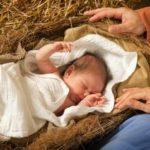 Ein Säugling liegt in Windeln gewickelt in einer Krippe