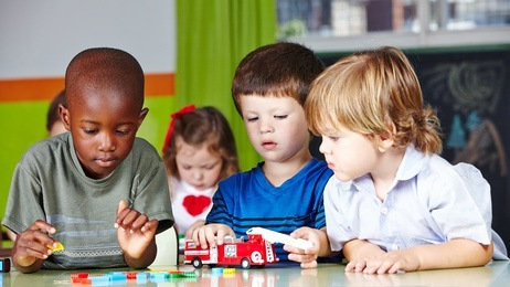 Kinder spielen zusammen im Kindergarten mit einer Feuerwehr