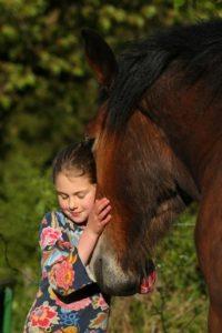 Mädchen schmust mit Pferd