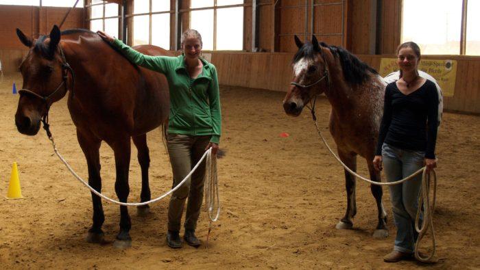 Ein Photo zeigt Sara und Julia mit ihren Pferden in der Reithalle.