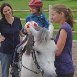 Ein Mädchen sitzt auf einem weißen Pferd und hält einen Stoffball in der Hand.