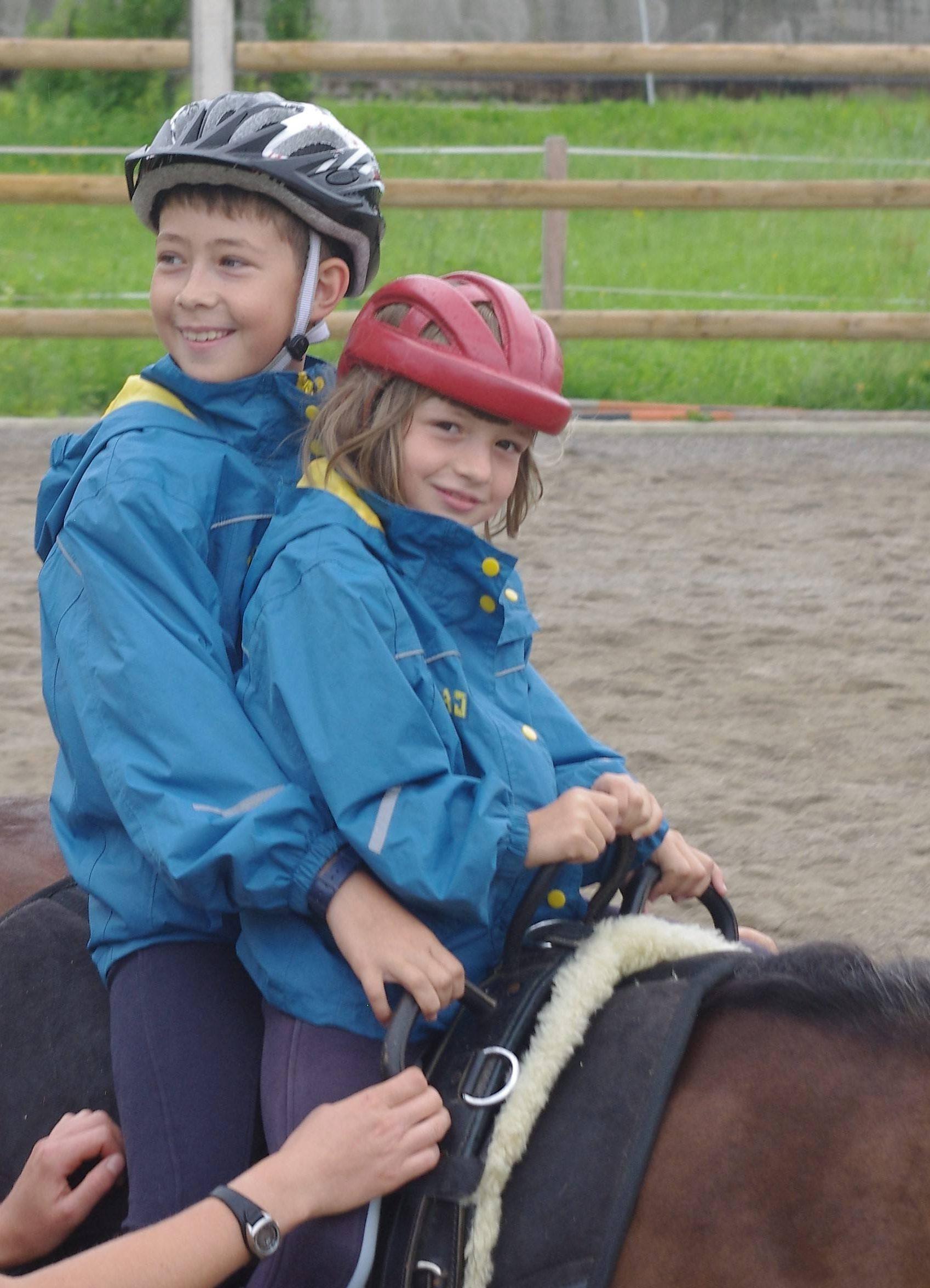 Zwei Kinder sitzen bei der heilpädagogischen Ferienmaßnahme zusammen auf einem Pferd