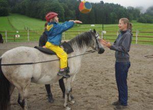 Ein Mädchen und ihre Reittherapeutin spielen Ball auf dem Pferd