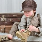 Ein kleiner Junge mit Ballonmütze sitzt vor alten Koffern und bindet sich hohe Schnürstiefel.