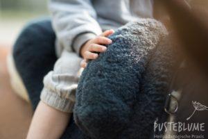 Bild einer Kinderhand auf einem Fellsattel in der Reittherapie