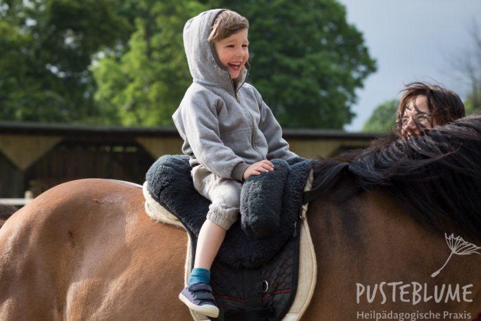 Ein kleiner Junge reitet im Schritt und lacht.