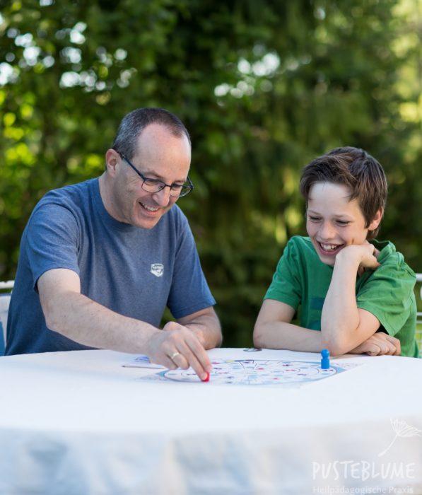 Unser Therapeut spielt mit einem Kind ein Lese-Rechtschreibspiel.