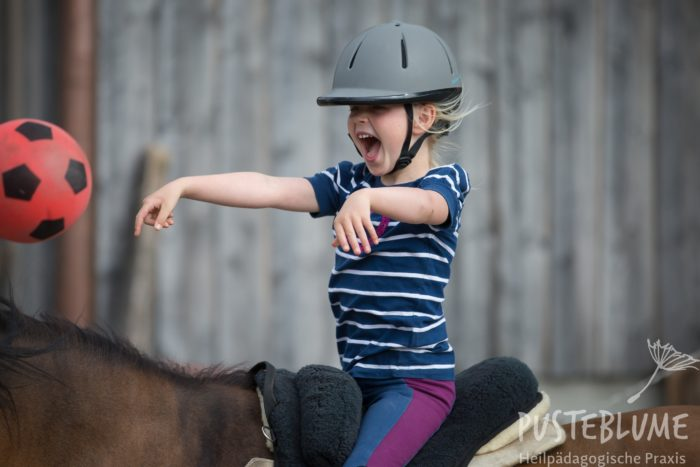 Ein Mädchen sitzt auf dem Pferd und wirft einen Ball.