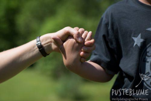 Eine Heilpädagogin reicht einem Jungen die Hand.