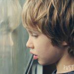 Ein autistischer Junge schaut durch eine Scheibe.