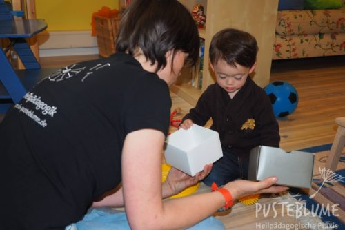 Eine Heilpädagogin und ein kleiner Junge spielen mit Schachteln.