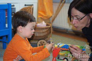 """Bild zum """"Spielen mit autistischen Kindern"""". Ein kleiner Junge spielt mit einer Fingerpuppe. Gesine spricht dazu."""