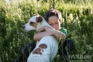 Ein Junge umarmt einen Hund und schließt dabei in tiefer Zuneigung die Augen.