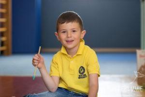 Ein kleiner Junge schaut lächelnd in die Kamera.