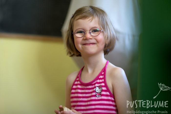 Ein kleines Mädchen grinst über das ganze Gesicht.