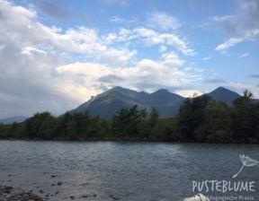 Im Vordergrund fließt die Tiroler Ache. Im Hintergrund sieht man die Berge und blauen Himmel.