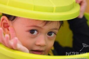 Ein kleiner Junge schaut aus einer Plastiktonne.