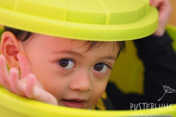 Ein kleiner Junge schaut aus einer Plastiktonne heraus.