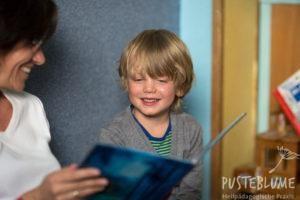 Gesine Herzog liest einem Jungen ein Bilderbuch vor.