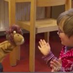 Kleines Mädchen spielt vergnügt mit einer Löwenhandpuppe.